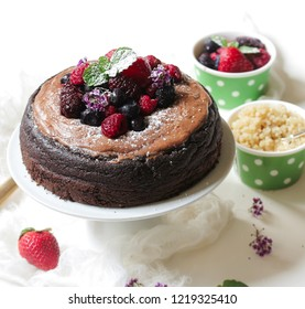 Homemade Chocolate Quinoa Cake topped with fruits and berries, selective focus
