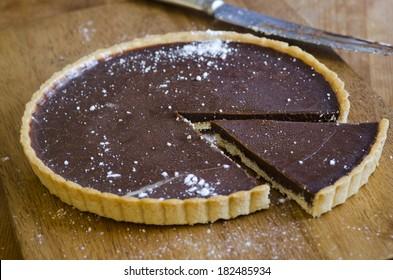 Homemade chocolate tart on a wooden board
