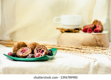 Homemade chocolate truffle with fresh raspberry in the green plate on white linen tablecloth backgound.