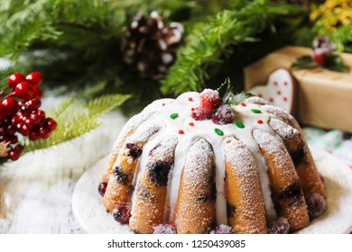 Homemade Christmas Bundt cake with White icing on festive holiday background, selective focus / X-mas mixed fruit cake
