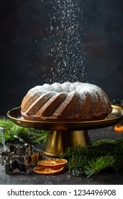 Homemade Christmas cake on a vintage stand sprinkled with powdered sugar, selective focus.