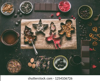 Homemade Christmas chocolate bars making. Christmas cutters with various toppings and flavorings. Melted chocolate in bowl with spoon on dark rustic kitchen table background, top view. Edible gifts
