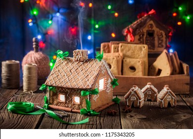 Homemade Christmas gingerbread cottage and Christmas lights on rustic table