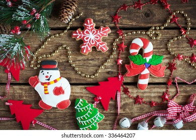 Homemade christmas gingerbreads painted as snowman, a red snowflake and Christmas tree with festive decoration on the wooden background with fir branches. Selective focus and place for text. Toned.