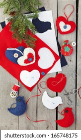 Homemade Christmas ornaments being made from felt, ribbon, and buttons.