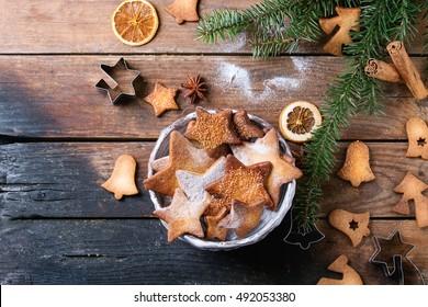L'étoile de Noël fait maison forme des biscuits de sucre de différentes tailles avec de la poudre à sucre, de la cannelle, du sapin vert et des cutters de biscuits sur une vieille surface en bois. Bonbons de Noël. Vue de dessus