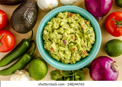 Homemade chunky guacamole in bright blue bowl surrounded by dip ingredients
