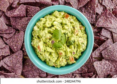 Homemade chunky guacamole in bright blue bowl surrounded by blue corn tortilla chips