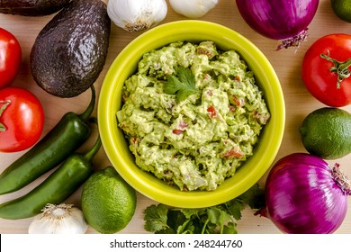 Homemade chunky guacamole in bright green bowl garnished with cilantro surrounded by dip ingredients