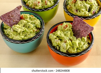 Homemade chunky guacamole in four colorful individual serving bowls garnished with blue corn tortilla chip