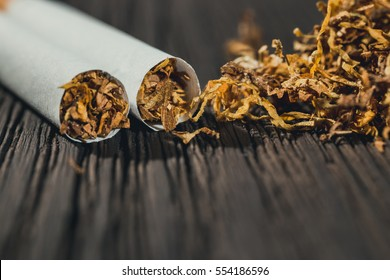 homemade cigarettes and tobacco on the brown wooden table, close up with copy space