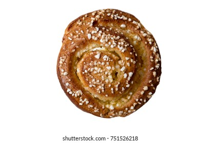 Homemade cinnamon bun decorated with crushed nib sugar isolated on white background.