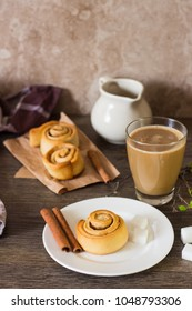Homemade cinnamon buns rolls or cinnabons served with coffee on rustic table. Sweet traditional dessert for breakfast. Copy space.