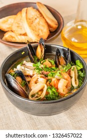 Homemade cioppino in a bowl and toast on a light rustic background - Italian-American seafood soup - fish, mussels, shrimp and squid.