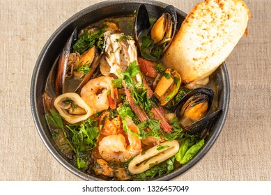 Homemade cioppino in a bowl and toast, top view - Italian-American seafood soup - fish, mussels, shrimp and squid.
