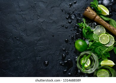Homemade citrus lemonade mojito with ingredients for making on a dark slate, stone or concrete background.Top view with copy space.