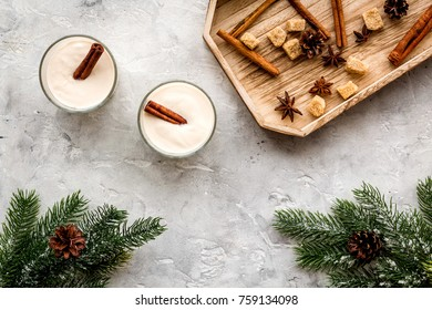 Homemade classic eggnog with cinamon and badian on wooden tray near spruce branch, pinecones on grey stone background top view