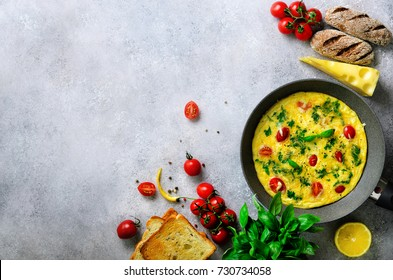 Homemade classic omelet with cherry tomatoes, cheese and herbs on grey concrete background. Frittata in a frying pan. Top view, copy space