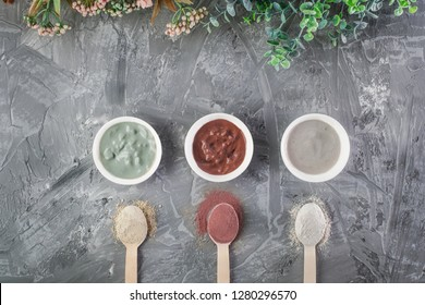 Homemade clay face masks on concrete background in white bowls. Three different types of clay. Nature skincare.