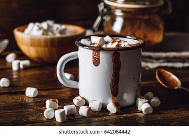 Homemade Cocoa Mug with Marshmallows. Jar of Cocoa Powder and Marshmallow Bowl on Backdrop.