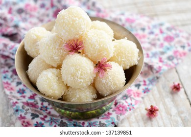 Homemade coconut balls decorated with little pink flowers in metal bowl, wooden background