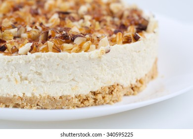 Homemade coconut cheesecake with caramel and assorted nuts