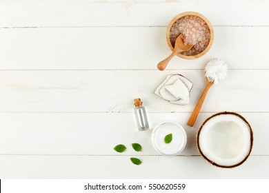 Homemade coconut products on white wooden table background. Oil, scrub, milk, lotion, mint and himalayan salt from top view. Good for space and background