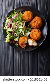 Homemade codfish cake and fresh salad closeup on a plate on the table. Vertical top view from above