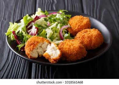 Homemade codfish cake and fresh salad closeup on a plate on the table. horizontal