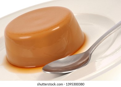 Homemade coffee flan in a plate close-up with a spoon
