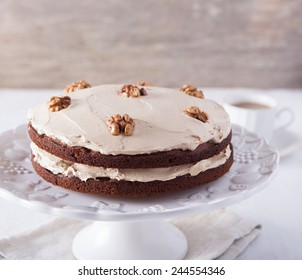Homemade coffee and walnut cake on the white wooden table, selective focus