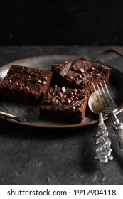 Homemade comfort food. Yummy chocolate brownies with dry srawberries pieces and choco drops on dark background