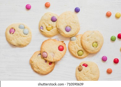 Homemade cookies with colorful, sugar coated chocolate candies on white wooden background for fun birthday party celebrations for small kids