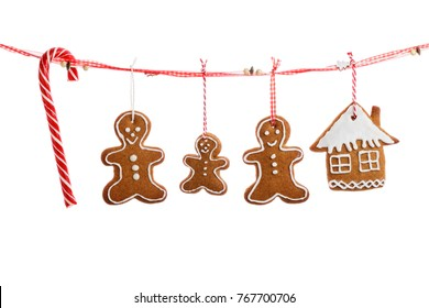 Homemade cookies in the form of Christmas decorations hanging on a red ribbon.  Isolated on a white background