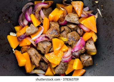 Homemade cooking traditional meat stew with beef, pumpkin, onions, fried in pan
