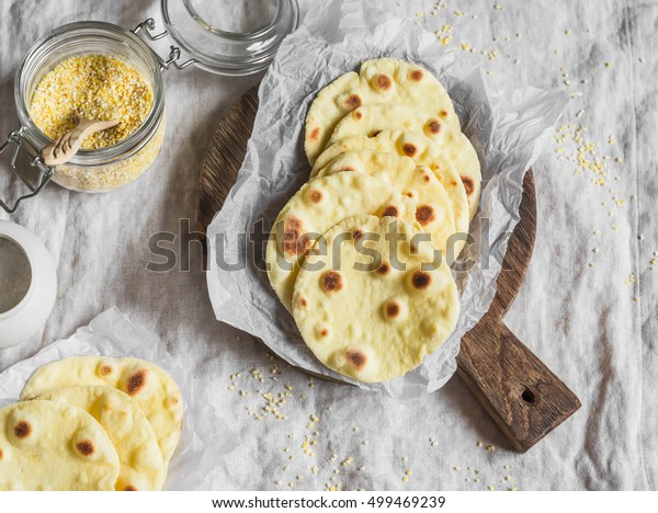 Homemade corn tortilla on a wooden rustic cutting board. On a light background, top view
