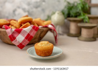 Homemade Cornbread Muffin Isolated on a Small Plate with a Wooden Bowl Full of Homemade Muffins, Slices, and Sticks Lined with Red & White Checked Napkin in the Background