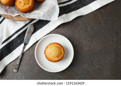 Homemade Cornbread Muffin Isolated on White Plate with Butter Knife Beside; Wooden Bowl of Muffins in Background; Black and White Kitchen Towel; Black Background
