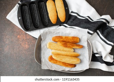 Homemade Cornbread Sticks on Parchment Paper in Pewter Tray; Cast Iron Cornbread Stick Pan in Background; Black and White Kitchen Towel; Black Background