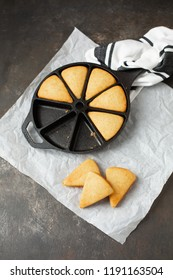 Homemade Cornbread Wedges in Cast Iron Skillet; Individual Slices Isolated on White Parchment Paper; Black & White Kitchen Towel in Background; Black Background