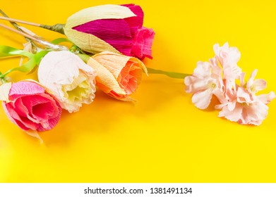homemade corrugated paper flowers on yellow background
