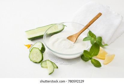 Homemade cosmetics with cucumber and sour cream on a white background. Detoxification skin vegetable masks.
