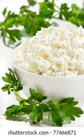 Homemade cottage cheese on a white bowl with fresh parsley.