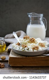 Homemade cottage cheese on wooden background with walnuts and honey
