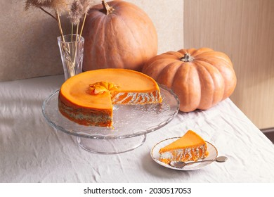 Homemade cottage cheese and pumpkin casserole with poppy seeds and orange and cut piece on a glass stand and pumpkins.