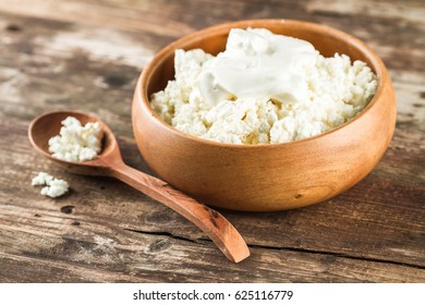 Homemade cottage cheese with sour cream in a round wooden bowl on a wooden table.