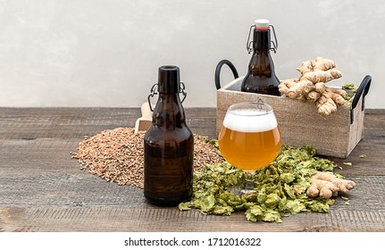Homemade craft ginger beer in a glass with dry hops and beer growlers on the wooden table