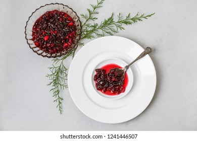 Homemade Cranberry Sauce on White Plates with Cedar Twigs on Gray Background