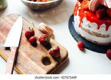 Homemade cream layer cake, fresh, colorful, and delicious dessert with juicy strawberries, sweet whipped cream, cream cheese and macaroons