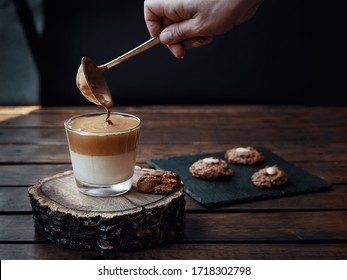 Homemade creamy Dalgona coffee along with some homemade cookies. Hand serving coffee with a spoon. Dark photography.